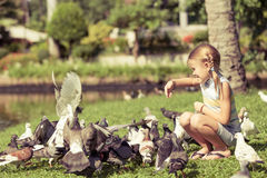小女孩哺养的鸽子在公园 免版税库存图片