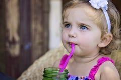 小女孩啜饮的柠檬水 免版税库存图片