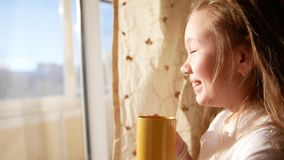 小女孩喝茶靠近windoe在日出 影视素材