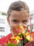 小女孩嗅到的花 免版税图库摄影
