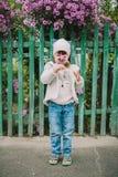 小女孩嗅花 在绿色fe背景  免版税库存照片