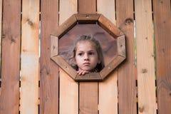小女孩在一个木房子里看窗口 库存照片