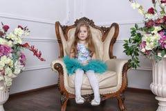 小女孩在一件美丽的礼服的一把椅子坐 库存照片