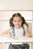 小女孩在一本拷贝书的文字字母表在书桌 图库摄影