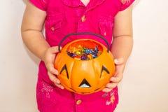 小女孩在万圣夜拿着与甜点的南瓜在手上, 库存图片