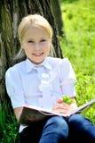 小女孩在与书的树附近坐在手上 图库摄影