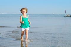 小女孩在与她的脚的海滩跑在海 免版税库存照片