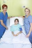 小女孩在与护士的医院病床上 库存图片