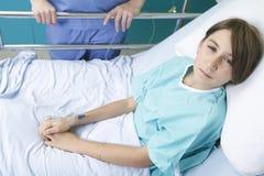 小女孩在与护士的医院病床上 免版税库存图片