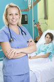 小女孩在与护士的医院病床上 免版税图库摄影