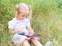 小女孩在与片剂个人计算机的公园坐晴天和戏剧 库存图片