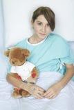 小女孩在与玩具熊的医院病床上 免版税库存照片