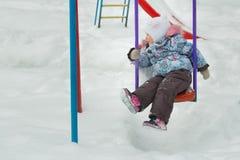 小女孩在与白色雪的冷淡的冬天操场摇摆覆盖物乘坐户外 库存图片