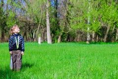 小女孩在与花包裹的绿草站立  图库摄影