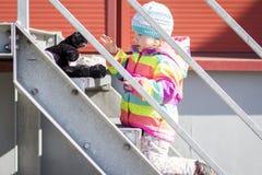 小女孩在与长毛绒玩具的金属楼梯使用 免版税库存图片