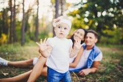 小女孩在休息说谎在草的父母背景的一年学会走在自然在公园 第一步o 免版税库存图片