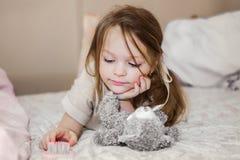 小女孩在使用与它的玩具熊的床上 免版税库存图片