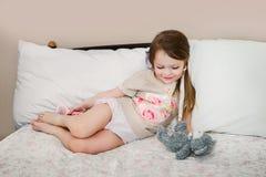 小女孩在使用与它的玩具熊的床上 库存图片
