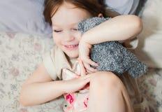 小女孩在使用与它的玩具熊的床上 免版税图库摄影