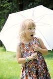小女孩在公园在伞下 库存图片