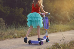 小女孩在公园学会乘坐滑行车在晴朗的夏日 活跃休闲和户外运动孩子的 库存照片
