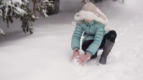 小女孩在冬天公园雕刻雪人 从天空落的雪 影视素材