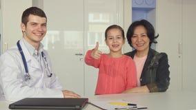 小女孩在医生附近显示她的赞许 库存照片