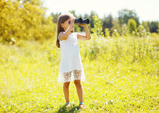 小女孩在双筒望远镜看户外在夏天 库存图片