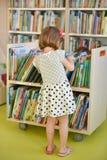 小女孩在图书馆里选择一本书 免版税库存照片
