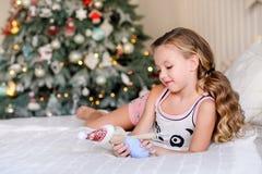 小女孩在圆锥形小屋附近坐 免版税库存图片
