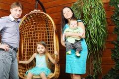 小女孩在垂悬的椅子和父亲,有婴孩的母亲坐 免版税库存照片