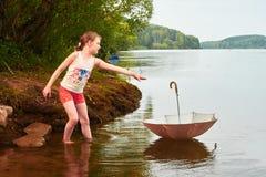 小女孩在多云天丢失了她的伞在湖 免版税库存图片