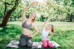 小女孩在她的妈妈以后重复ecxercise 他们保留在臀部的左手,并且右手悬而未决 库存图片