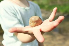 小女孩在她的手上的拿着一块石头 石头是特写镜头 女孩不聚焦 图库摄影