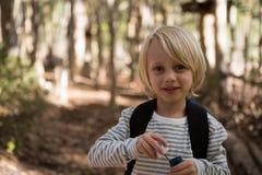 小女孩在她的手上的拿着泡影鞭子在森林里在一个晴天 免版税库存图片