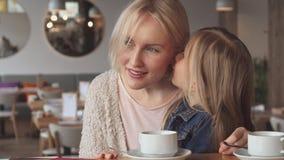 小女孩在她的母亲` s耳朵耳语在咖啡馆 库存照片