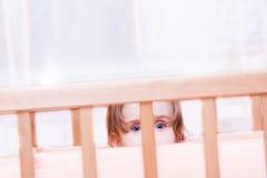 小女孩在小儿床坐 免版税库存图片