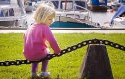 小女孩在小船小游艇船坞 库存照片