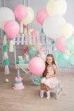 小女孩在屋子装饰的五颜六色的baloons里坐 库存照片
