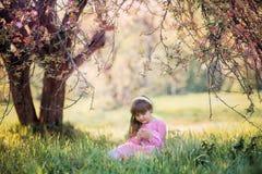 小女孩在开花的苹果树下 免版税库存照片