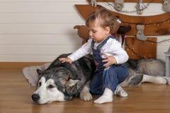 小女孩在房子和爱斯基摩狗里 免版税库存图片