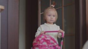 小女孩在房子里播放一辆玩具摇篮车 股票视频