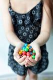 小女孩在手上的拿着糖果 免版税库存图片