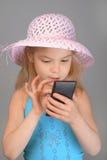 小女孩在手机的读书sms 免版税库存照片