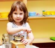 小女孩在手研磨机的研磨咖啡 免版税图库摄影