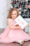 小女孩在打开礼物的圣诞树下 库存图片
