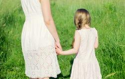 小女孩在拿着她的母亲的草甸由手 免版税库存照片