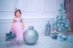 小女孩在摆在圣诞树附近的美丽的时尚白花礼服穿戴了 库存图片