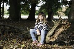 小女孩在日落的森林里 库存照片