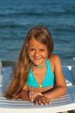 小女孩在明媚的阳光下在海边 免版税图库摄影